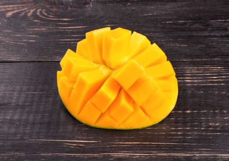 mango: Half mango fruit cut into cubes on a dark table