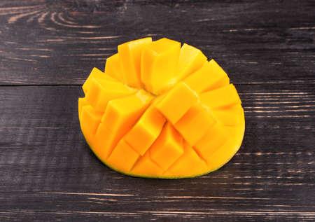 mango fruta: La mitad de la fruta del mango cortado en cubos en una mesa oscura