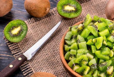 Preparing fresh salad from tropical fruit kiwi