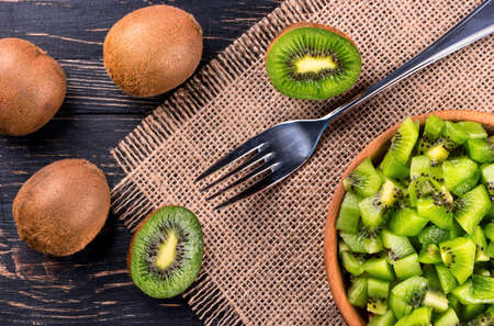 kiwi: Wooden bowl with a salad of kiwi fruit and a fork on the table top view