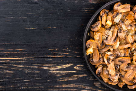 pan: Part of the frying pan with fried mushrooms champignon on empty wooden background Stock Photo