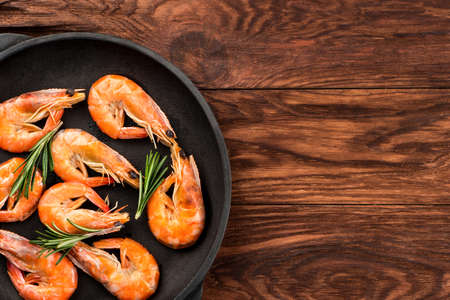 Part of the frying pan with fried shrimp and rosemary on a blank table