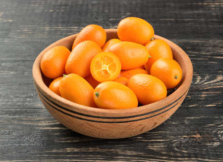 cumquat: Bowl full of fresh fruit kumquat on the wooden background Stock Photo