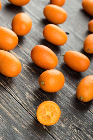 cumquat: Scattered fresh fruit kumquat on the wooden background Stock Photo