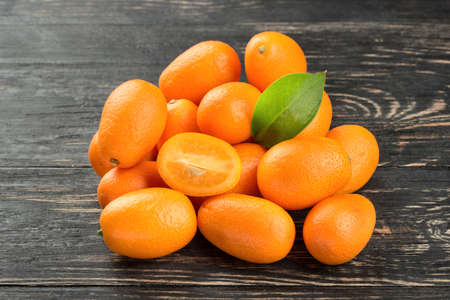 cumquat: Pile of fresh fruit kumquat on a dark table