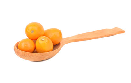 cumquat: Wooden spoon filled with fresh fruit kumquat on white background Stock Photo