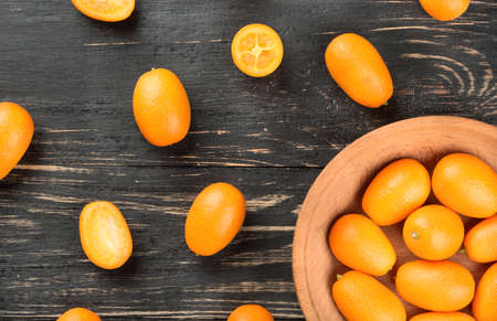 cumquat: Part bowls with kumquat and scattered fruit on wooden background