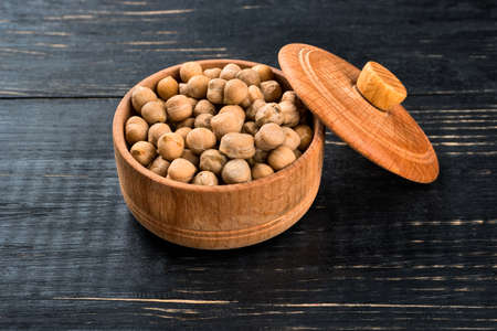 capacitance: Dry chickpeas in a wooden capacitance on a dark table Stock Photo