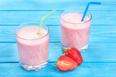 Two glasses of fresh strawberry cocktail with milk on a blue wooden background