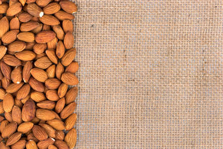 sackcloth: Scattered dry almond nuts on a blank sackcloth