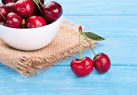 Two red cherries with a full bowl of berries on sacking and blue table closeup