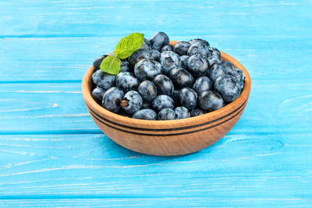 Ripe blueberries with mint leaves in a bowl on a wooden background