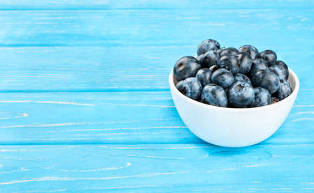 White ceramic bowl with blueberries on a wooden background Stock Photo