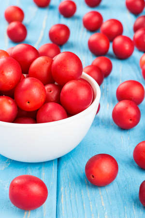 White ceramic bowl full of red cherry plums with scattered berries on table Stock Photo