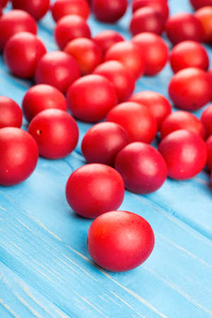 Scattered red cherry plum on wooden background close-up