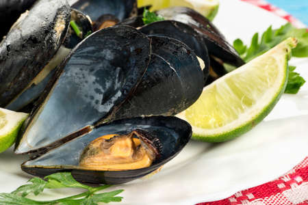Open mussels cooked with ingredients on a plate, close-up Stock Photo