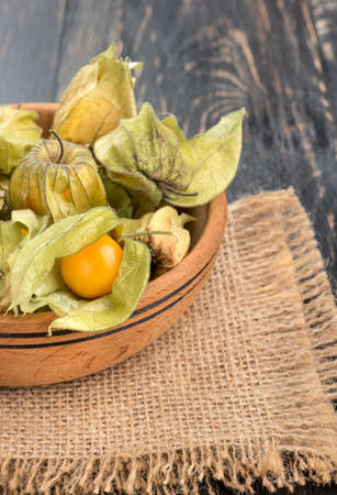 husk tomato: Part bowls filled with physalis in the husk on sackcloth and table