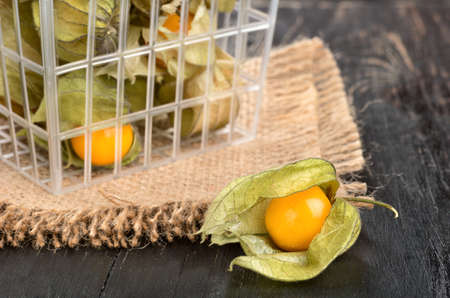 Fresh berry physalis fruit in the container on table and sacking, closeup Stock Photo