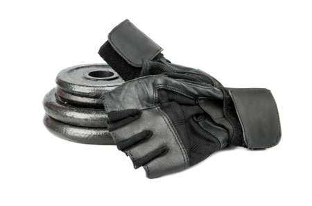body toning: Stack of weight plates and old fitness gloves on a white background