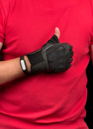 Young athlete with fitness bracelet and gloves on a hand shows Like