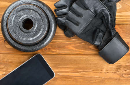 muscle toning: Weight plates, gloves and smartphone on wooden background, top view