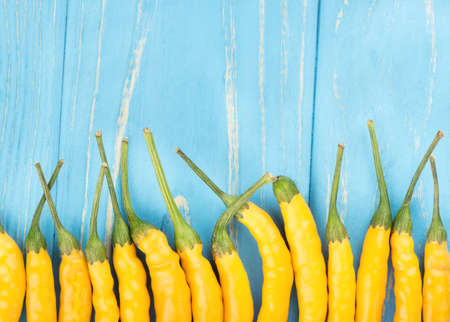 capsaicin: Built abreast yellow hot peppers on empty wooden background