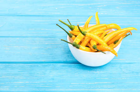 capsaicin: White ceramic bowl with yellow chili peppers on a wooden background