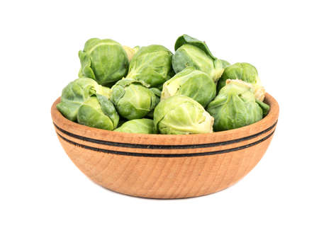 Wooden bowl full of fresh brussel sprouts on a white background