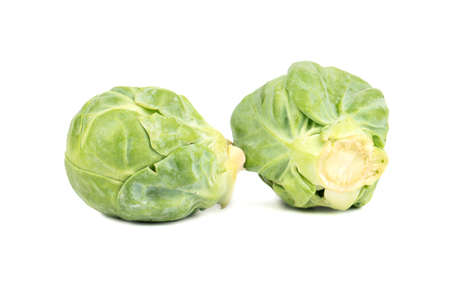 Two raw brussel sprouts on a white background