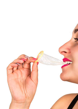 Cheerful woman holding in her teeth open a condom