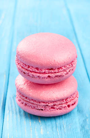 Two pink macaroon with cream on a wooden background Stock Photo