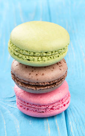 Stack of of multicolored macaroon on a wooden background close up Stock Photo