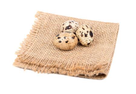 Trzy surowego przepiórki jajka na burlap i białym tle