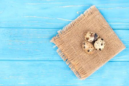 Trzy surowego przepiórki jajka na burlap i pustym drewnianym tle, odgórny widok Zdjęcie Seryjne