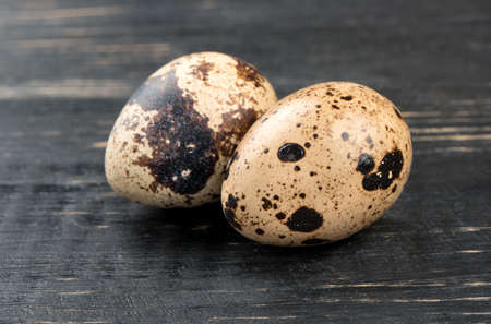 Two raw quail eggs on dark wooden background