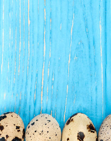 Scattered raw quail eggs on wooden background, top view Zdjęcie Seryjne