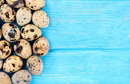 Scattered raw quail eggs on wooden background, top view Stock Photo