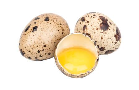 Broken raw quail egg on white background