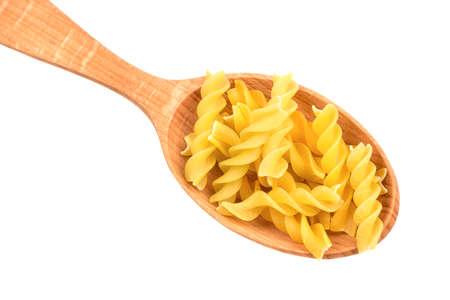 Pasta fusilli in a wooden spoon on white background, closeup