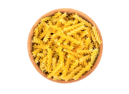 Uncooked pasta fusilli in a wooden bowl on a white background, top view