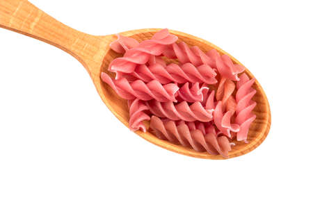Red fusilli pasta in spoon on white background, closeup