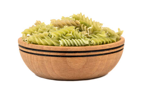 Wooden bowl of green raw pasta fusilli on white background