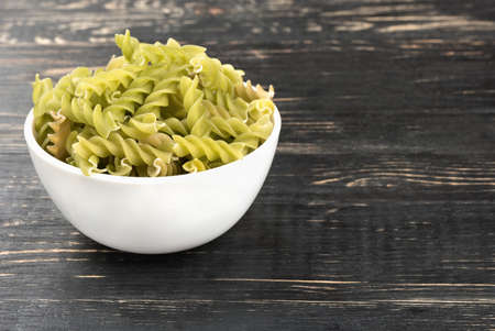 White bowl with raw pasta fusilli on wooden background