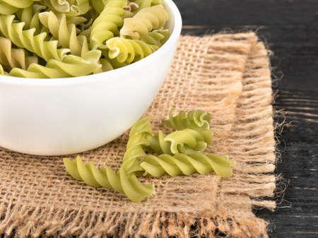 Green bowl of raw pasta fusilli on sackcloth close up