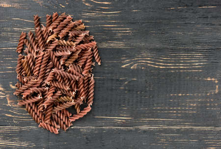 Small dark pile of pasta fusilli on an empty wooden background