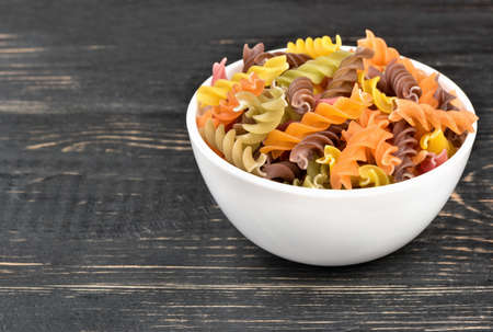 White bowl with multi-colored raw pasta fusilli
