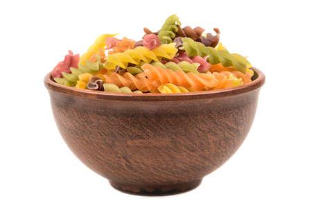 Raw colored pasta fusilli in a bowl on white background