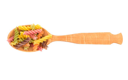 Wooden spoon with colored pasta fusilli on white background, top view Stock Photo