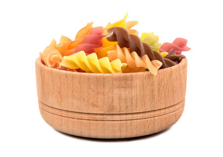 Colored pasta fusilli in a wooden bowl on white background Stock Photo