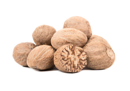 Bunch of nutmeg nuts with half on white background